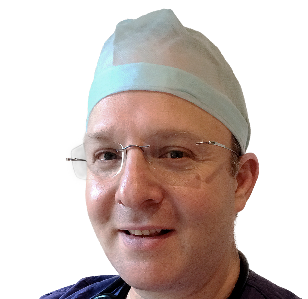 A man in surgical scrubs smiles at the camera. He is a Fertility Specialist and Gynaecologist. It looks like he is in surgery. He is wearing a hair covering that is light blue and used during surgery. He is also wearing reading glasses that have no frames. He is Caucasian with blue/green eyes.