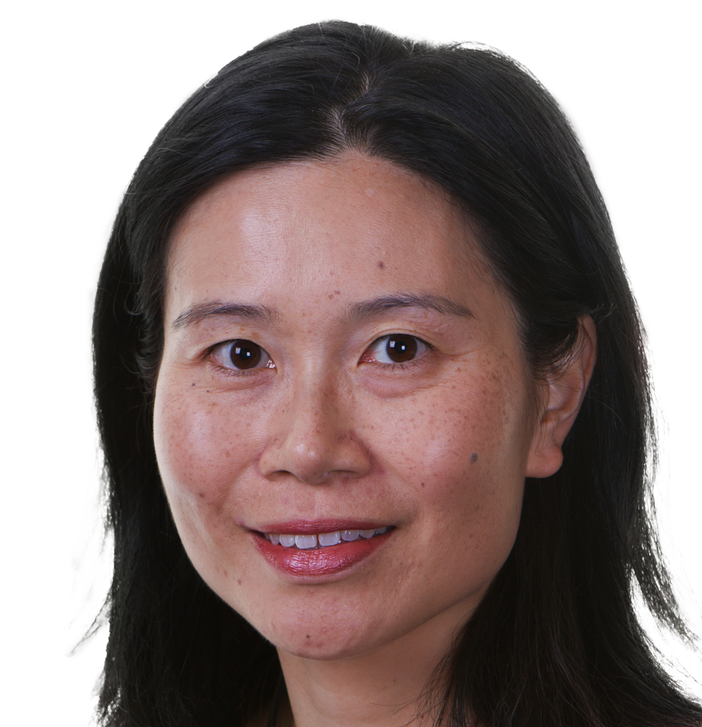 A woman smiles into a camera. She is Asian, with shoulder length black hair and dark brown eyes. She is wearing minimal makeup, with her pink lipstick bringing out the pink in her cheeks.