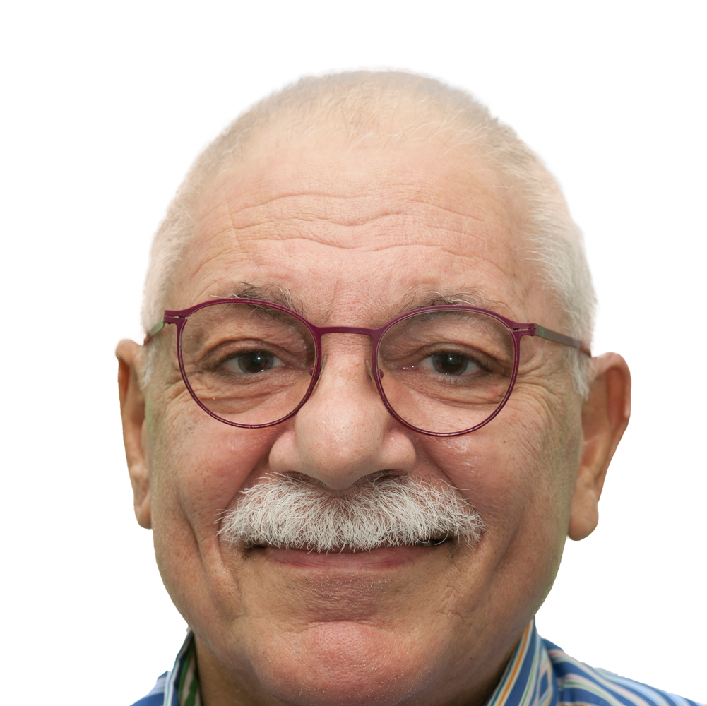 An older man half smiles at the camera. He has a thick white mustache and short white hair. He has hazel coloured eyes, and wears oval shaped glasses that have a dark red frame. He is wearing a shirt with white and blue stripes.