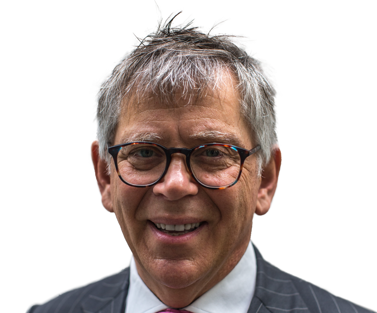 A man smiles at the camera. He has grey hair and hazel coloured eyes. He wears glasses with a tortoise-shell colour frame. He is wearing a grey suit jacket with a pale blue shirt and a red tie.